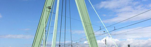 Schrägseilbrücke mit grünem Pylon vor blauem Himmel